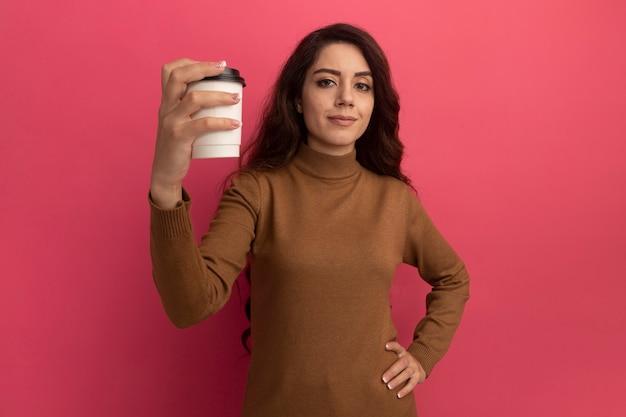 Confiant jeune belle fille portant un pull à col roulé tenant une tasse de café isolé sur un mur rose