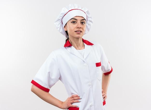 Confiant jeune belle fille en uniforme de chef mettant les mains sur la hanche