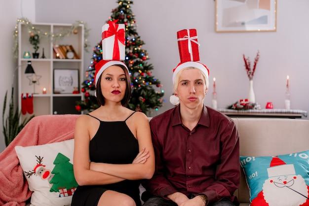 Confiant jeune couple à la maison à l'époque de noël portant bonnet de noel assis sur un canapé avec des paquets-cadeaux sur la tête dans le salon fille assise avec une posture fermée à la fois regardant la caméra