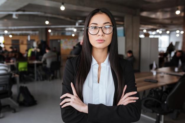 Confiant jeune femme d'affaires asiatique debout avec les bras croisés au bureau