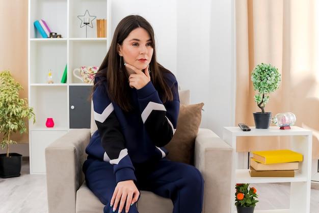 Confiant jeune femme assez caucasienne assise sur un fauteuil dans un salon conçu mettant la main sur la jambe touchant le menton et regardant droit