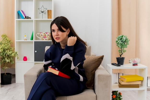 Confiant jeune femme assez caucasienne assise avec les jambes croisées sur un fauteuil dans le salon conçu à la recherche de livre de maintien tout droit et en gardant le poing en l'air