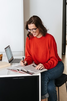 Confiant jeune femme assise à la table de la cuisine à la maison, étudiant avec ordinateur portable et classeur
