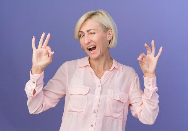 Confiant jeune femme blonde slave un clin de œil et de faire des signes ok isolés sur fond violet