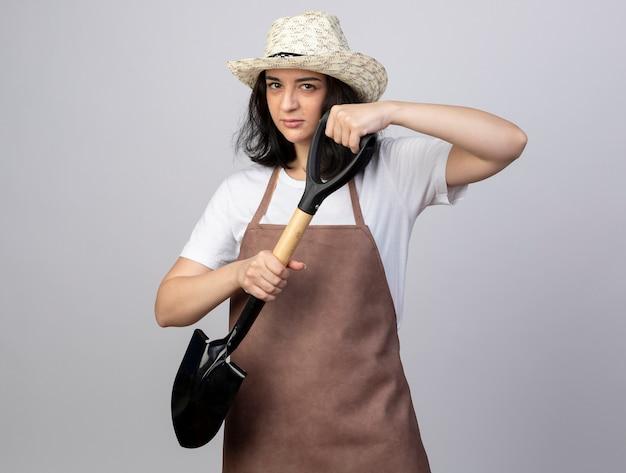 Confiant jeune femme brune jardinière en uniforme portant chapeau de jardinage détient pelle sur blanc