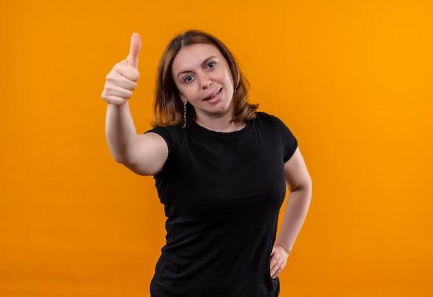Confiant jeune femme décontractée montrant le pouce vers le haut avec la main sur la taille sur l'espace orange isolé avec copie espace