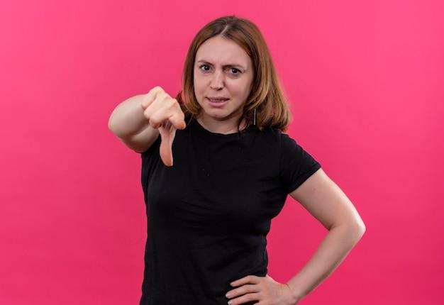 Confiant jeune femme décontractée pointant avec la main sur la taille sur un espace rose isolé avec copie espace