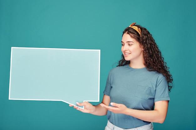 Confiant jeune femme en foulard de cheveux pointant sur la bannière en forme de nuage de dialogue tout en expliquant les informations sur le bleu