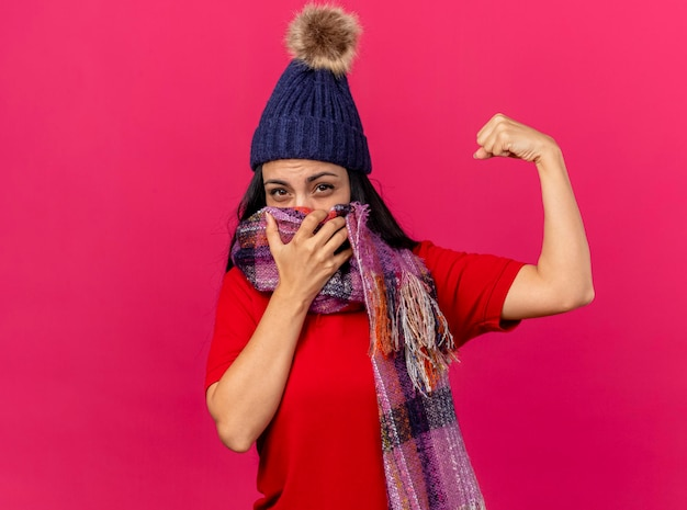 Confiant jeune femme malade portant un chapeau d'hiver et une écharpe couvrant la bouche avec un foulard à l'avant faisant un geste fort isolé sur un mur rose avec copie espace