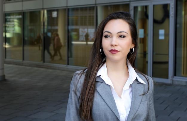Confiant jeune femme manager marchant en plein air dans un cadre urbain moderne