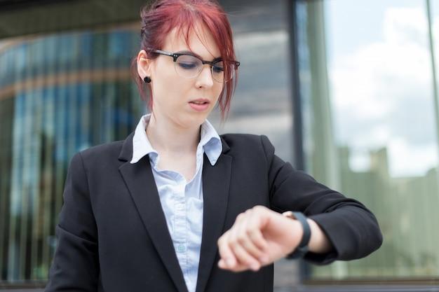 Confiant jeune femme manager en plein air vérifiant l'heure sur sa montre