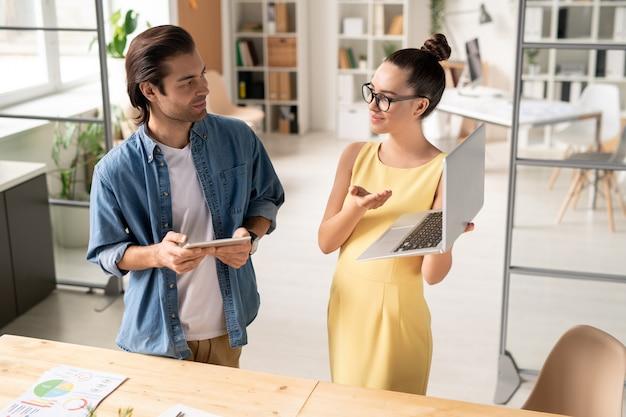 Confiant jeune femme en robe jaune tenant un ordinateur portable et pointant sur l'écran tout en présentant un projet en ligne à un collègue au bureau