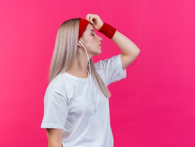Confiant jeune femme sportive avec des accolades sur des écouteurs portant un bandeau et des bracelets se tient sur le côté mettant la main sur le front isolé sur un mur rose