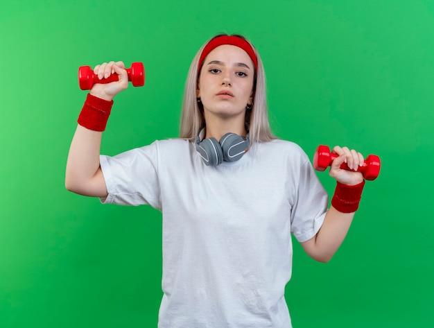 Confiant jeune femme sportive avec des accolades portant un bandeau et des bracelets avec des écouteurs sur le cou tient des haltères à l'avant isolé sur le mur vert