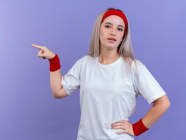 Confiant jeune femme sportive avec des accolades portant des points de bandeau et de bracelets sur le côté isolé sur mur violet