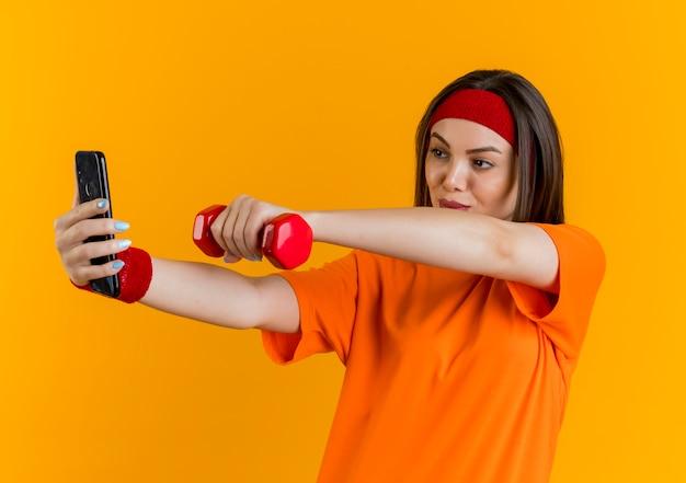 Confiant jeune femme sportive portant un bandeau et des bracelets s'étendant sur des haltères et prenant selfie