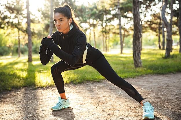 Confiant jeune femme sportive se réchauffer avant de faire du jogging dans le parc, écouter de la musique avec des écouteurs sans fil