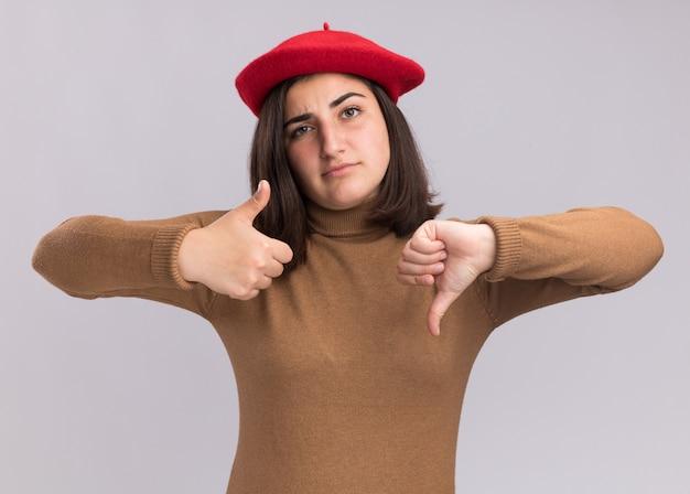 Confiant jeune fille assez caucasienne avec chapeau béret pouces vers le haut et pouces vers le bas sur blanc