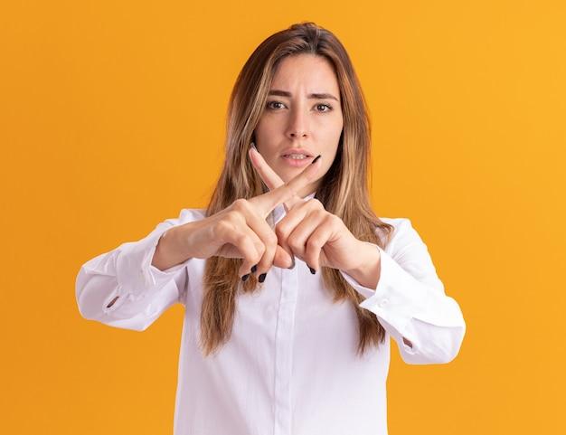 Confiant jeune fille assez caucasienne croise les doigts ne faisant aucun signe sur orange