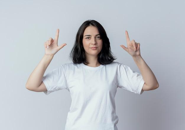 Confiant jeune fille assez caucasienne pointant avec les doigts vers le haut isolé sur fond blanc
