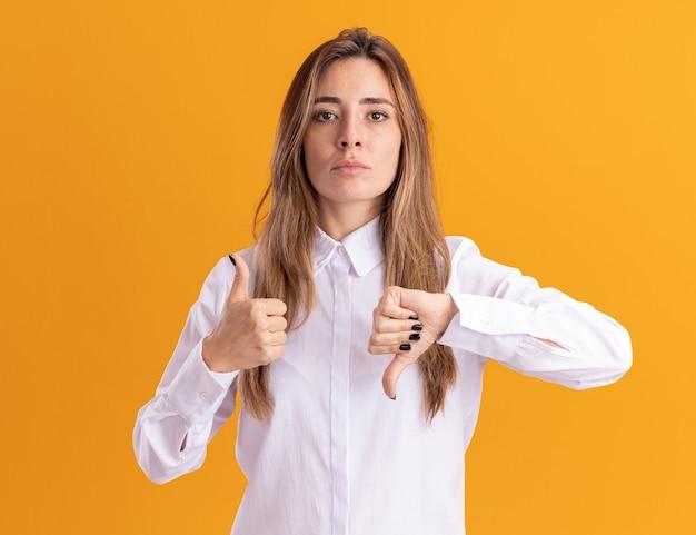 Confiant jeune fille assez caucasienne pouces vers le haut et pouces vers le bas sur orange