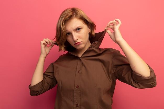 Confiant jeune fille blonde saisissant le col de la chemise