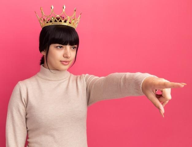 Confiant jeune fille brune caucasienne avec couronne regarde et pointe sur le côté rose