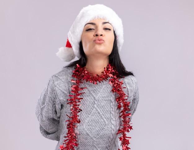 Confiant jeune fille caucasienne portant chapeau de noël et guirlande de guirlandes autour du cou en gardant les mains derrière le dos en regardant la caméra faisant baiser geste isolé sur fond blanc avec espace copie