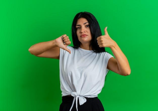 Confiant jeune fille caucasienne pouces vers le haut et pouces vers le bas
