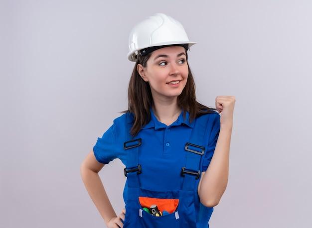 Confiant jeune fille constructeur avec casque de sécurité blanc et uniforme bleu lève le poing sur fond blanc isolé avec copie espace