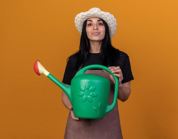 Confiant jeune fille de jardinier caucasien en uniforme et chapeau tenant un arrosoir