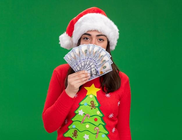 Confiant jeune fille de race blanche avec bonnet de noel détient de l'argent isolé sur fond vert avec espace copie