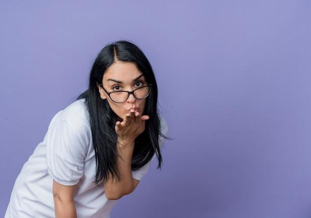 Confiant jeune fille de race blanche brune à lunettes optiques envoie baiser avec la main isolée sur le mur violet