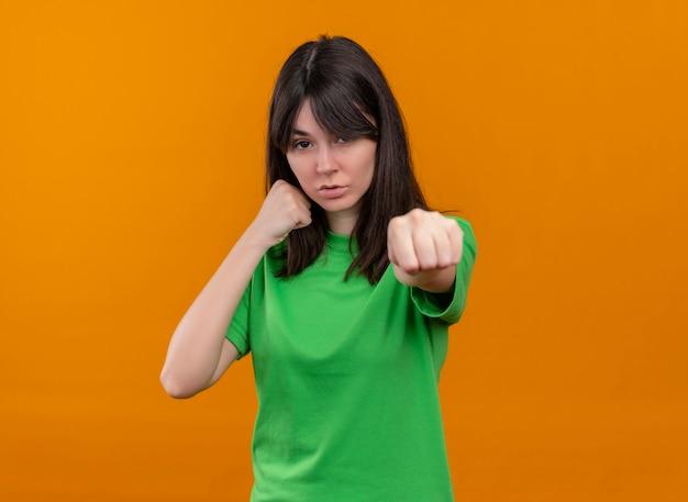 Confiant jeune fille de race blanche en chemise verte fait semblant de punch sur fond orange isolé