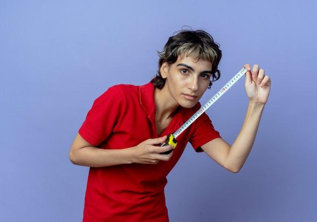Confiant jeune fille de race blanche avec coupe de cheveux de lutin tenant un mètre ruban isolé sur fond violet avec espace de copie