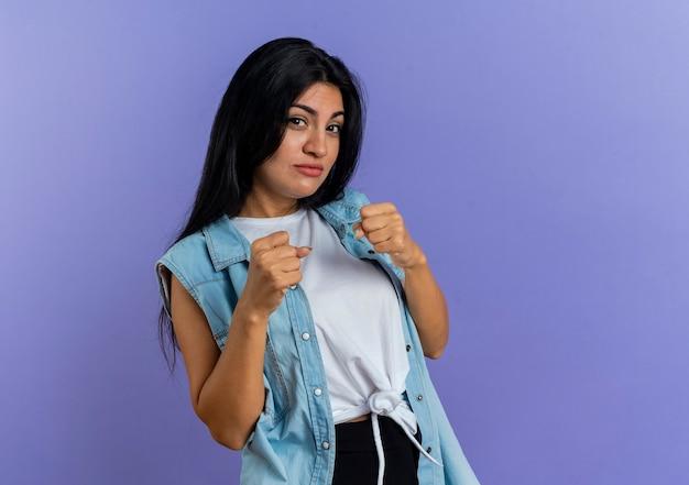 Confiant jeune fille de race blanche garde les poings prêts à poinçonner isolé sur fond violet avec copie espace