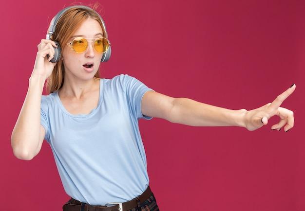 Confiant jeune fille rousse au gingembre avec des taches de rousseur dans des lunettes de soleil et sur les écouteurs à la recherche et pointant sur le côté rose