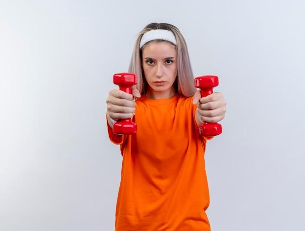 Confiant jeune fille sportive caucasienne avec des accolades portant bandeau et bracelets