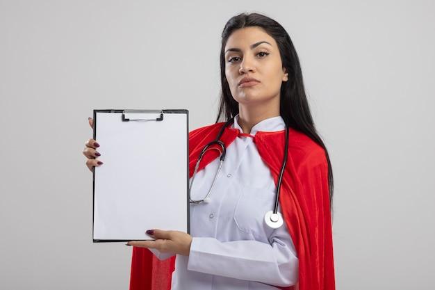 Confiant jeune fille de super-héros de race blanche portant un stéthoscope montrant le presse-papiers en regardant la caméra isolée sur fond blanc avec espace de copie