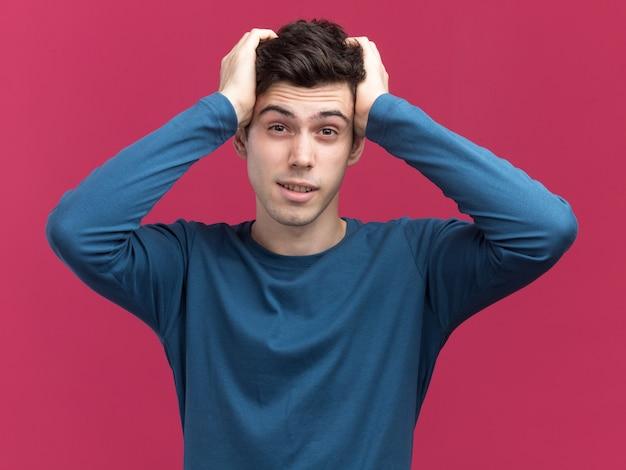 Confiant jeune garçon caucasien brune met les mains sur la tête en regardant la caméra sur rose