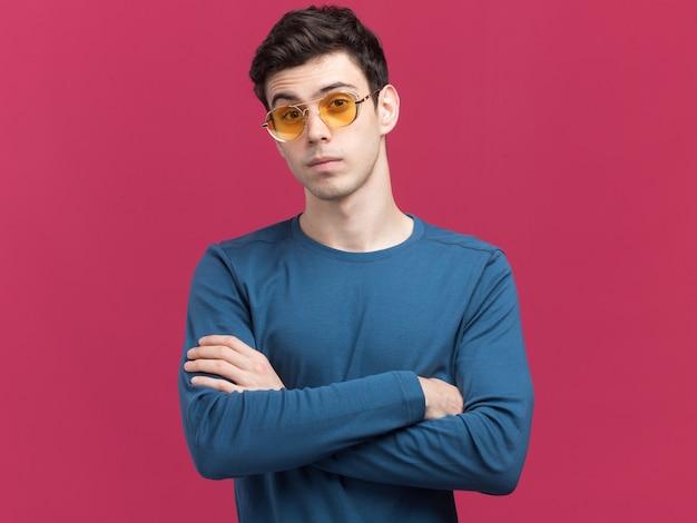 Confiant jeune garçon de race blanche brune à lunettes de soleil debout avec les bras croisés