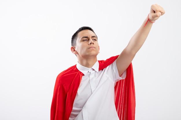 Confiant jeune garçon de super-héros en cape rouge levant le poing vers le haut à côté isolé sur fond blanc avec espace de copie