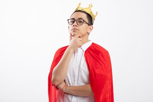 Confiant jeune garçon de super-héros en cape rouge portant des lunettes et une couronne regardant la caméra toucher le menton isolé sur fond blanc avec copie espace
