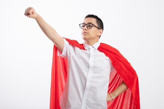 Confiant jeune garçon de super-héros en cape rouge portant des lunettes en gardant la main sur la taille en regardant côté étirant le poing isolé sur fond blanc