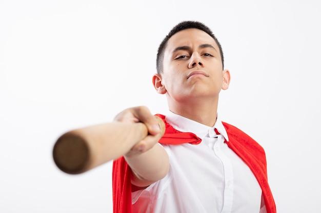 Confiant jeune garçon de super-héros en cape rouge qui s'étend de la batte de baseball vers la caméra en regardant la caméra isolée sur fond blanc