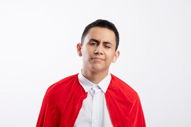 Confiant jeune garçon de super-héros en cape rouge regardant la caméra et un clin d'oeil isolé sur fond blanc avec espace de copie