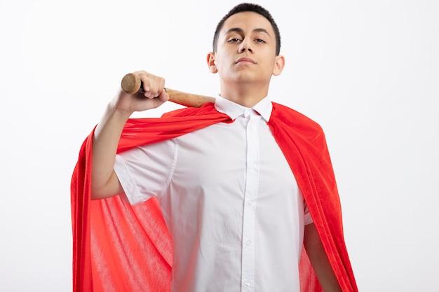 Confiant jeune garçon de super-héros en cape rouge tenant une batte de baseball sur l'épaule en regardant la caméra isolée sur fond blanc