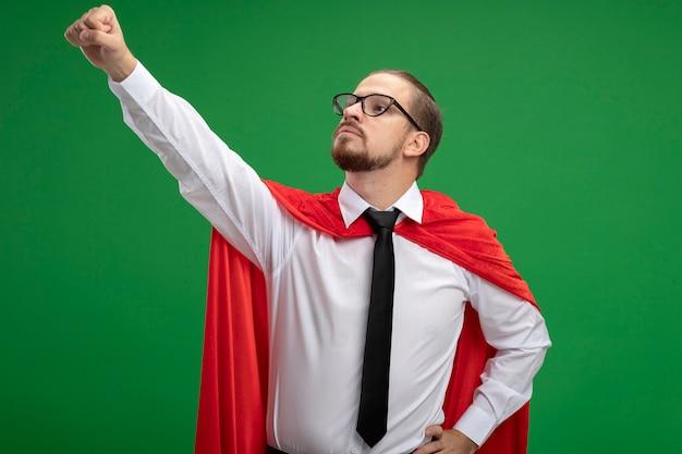 Confiant jeune gars de super-héros portant une cravate et des lunettes levant le poing isolé sur vert