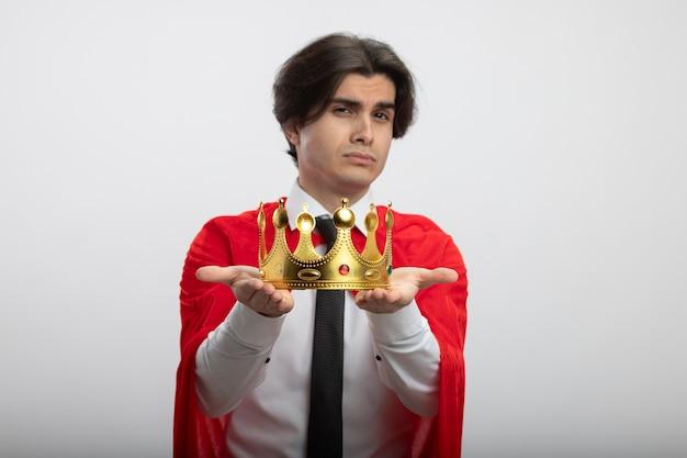 Confiant jeune gars de super-héros portant une cravate tenant la couronne à la caméra