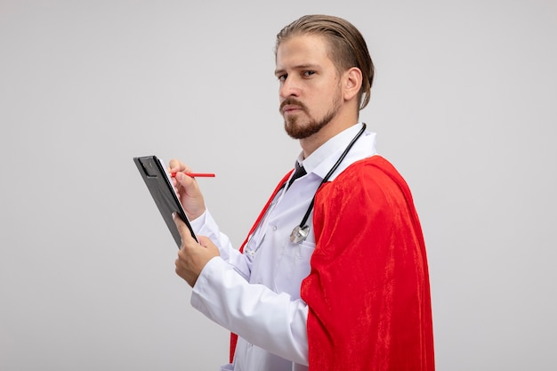Confiant jeune gars de super-héros portant une robe médicale avec stéthoscope écrit sur le presse-papiers isolé sur fond blanc